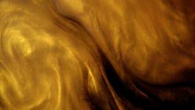 Tinta o polvo de oro que crea formaciones abstractas de la nube Fondos del arte almacen de metraje de vídeo
