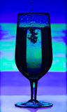 Tinted glass of champagne with splashes of liquid on abstract blurred background. Royalty Free Stock Photography
