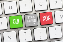 Tinted glass question and answer Yes and No in French. Tinted glass question and answer Yes and No  on a white keyboard Royalty Free Stock Photo