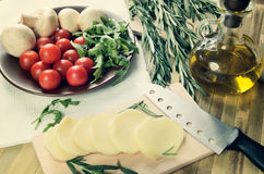 Tinted image cheese, tomatoes and herbs on a kitchen table top v Stock Images