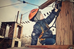 Tinted image little boy sits on suspension bridge and adjusts eq Stock Photo