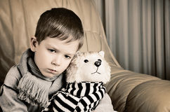 Tinted image sad little boy hugging toy dog Stock Images