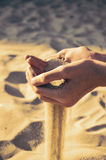 Tinted image sand pours out of the female hands. Horisontal Royalty Free Stock Photos