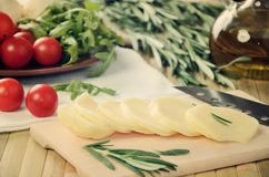 Tinted image sliced cheese, tomatoes and herbs on a kitchen tabl Royalty Free Stock Photos