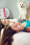Tinted image two girls with a Pomeranian lay on the bed and laug Royalty Free Stock Photography