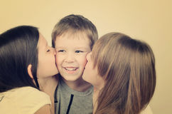 Tinted image two teens girls kissing little laughing boy. Two teens girls kissing little laughing boy. tinted image horizontal Royalty Free Stock Photography