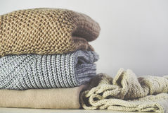 Tinted image warm sweaters are stacked on the table on a light g Royalty Free Stock Images