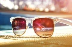 Tinted sunglasses reflecting pool. Dark tinted sunglasses with drops of water reflecting pool. Bright sunny day Stock Photo