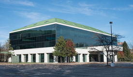 Tinted Window Building with Green Roof. Modern building with lots of tinted windows & green metal roof Stock Photo