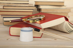 Tinteiro e penholder com a pena no desktop Agudeza na pena O fundo dos livros Foto de Stock
