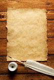 Tintenfaß und Feder auf einem alten Papier Stockfotografie