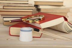 Tintenfaß und Penholder mit Stift auf dem Desktop Schärfe auf dem Stift Der Hintergrund der Bücher Stockfoto