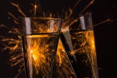 Tintinee los vidrios con el fondo de los fuegos artificiales en la Noche Vieja Fotos de archivo libres de regalías