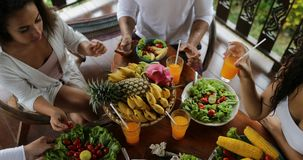 Tintineo Juice Glasses de la gente, tabla con los platos de frutas tropicales y consumición de los amigos de la opinión de ángulo almacen de metraje de vídeo