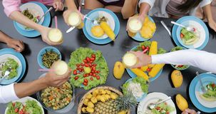 Tintineo Juice Glasses de la gente, tabla con los platos de frutas tropicales y consumición de los amigos de la opinión de ángulo almacen de video