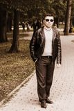 Young handsome man standing in a park in sunglasses and a leather jacket royalty free stock photography