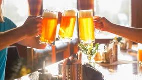 Tintinnio con gli amici che usando il vetro di birra fotografie stock