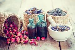 Tintura, cesta com botões cor-de-rosa, alfazema e flores secadas no almofariz Imagem de Stock
