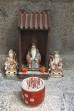 Tiny altar with incense and porcelain statues in a Chinese temple Royalty Free Stock Photo