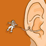 Tiny astronaut exploring floating out of human ear Royalty Free Stock Photos