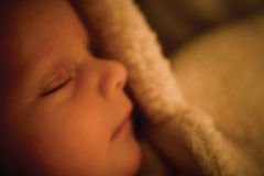 Tiny baby asleep in furry baby grow Stock Images