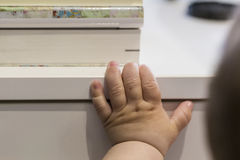Tiny baby hand hanging on a white wood Stock Photos