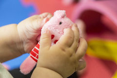 Tiny baby hands playing a pig plush toy Stock Photo