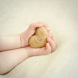 Tiny baby hands to hold the wooden heart Royalty Free Stock Photos