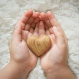 Tiny baby hands to hold the wooden heart Stock Photo
