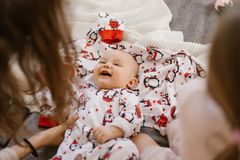 Tiny baby lies on a blanket and smiles at his mom royalty free stock image