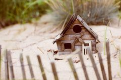 Tiny beachfront bird house in the sand royalty free stock photography