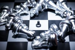Tiny black chess surrounded by a number of fallen big silver che. Ss pieces , business strategy concept stock photos