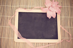 Tiny blackboard on bamboo with pink flower Royalty Free Stock Photos