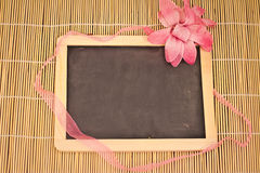 Tiny blackboard on bamboo with pink flower Royalty Free Stock Images