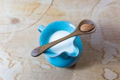 Tiny blue ceramic pitcher of almond milk, centered, wood spoon with a single almond balanced over top. Wood table, horizontal view Stock Photography