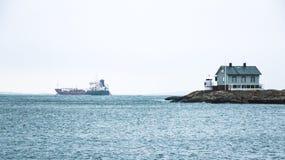 Tiny blue lighthouse on swedish coastline. With big boat on background Stock Photo