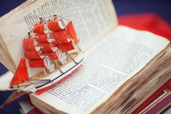 Tiny boat over an opened book's page composition Royalty Free Stock Photos
