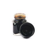 Tiny bottle filled with black ink Stock Photos