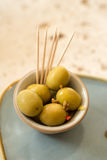 A Tiny Bowl of Whole Green Olives and Some Toothpicks Stock Images