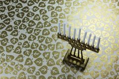 Tiny brass Hanukkah menorah with white candles on a background of metallic gold leaves. Horizontal aspect, space for text Stock Photography
