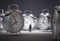 Tiny businessman with alarm clocks Royalty Free Stock Photo