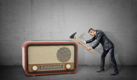 A tiny businessman on concrete background tries to destroy a large retro radio set with a broken hammer. Old technologies at work. Modernization attempt stock photos