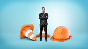 A tiny businessman with crossed hands standing beside giant striped traffic cones and an orange helmet. Road works. Highway to success. Small repair business Royalty Free Stock Photo