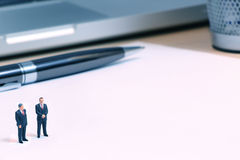 Tiny businessman dolls and contract Royalty Free Stock Image