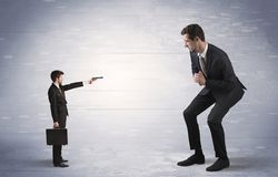 Small businessman shooting giant businessman royalty free stock image