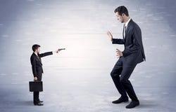 Small businessman shooting giant businessman stock photos