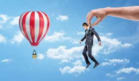 A tiny businessman held by a giant hand and hanging among blue sky near a striped air-balloon. royalty free stock images