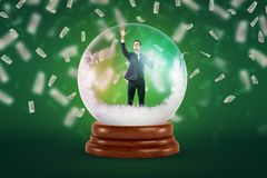 A tiny businessman inside a snowy crystal ball on a green background with dollar bills falling all around the place.