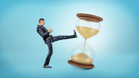 A tiny businessman kicks and shakes a large hourglass with half of its sand already in the lower chamber. Royalty Free Stock Photos