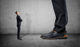 Tiny businessman looking up on huge legs of another man stock photos